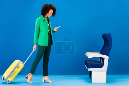Photo for Smiling african american woman holding travel bag and using smartphone on blue background - Royalty Free Image