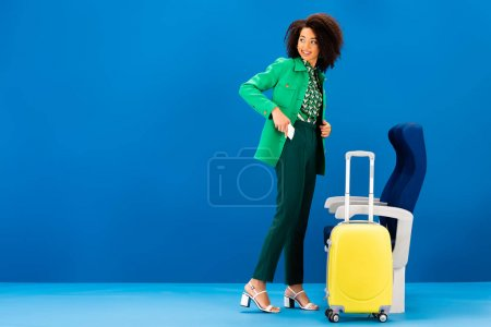 smiling african american woman putting in pocket smartphone and standing near travel bag and seats on blue background
