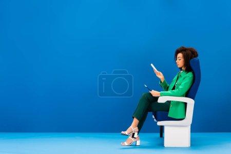 Photo pour Vue latérale de la femme afro-américaine assise sur un siège et tenant un smartphone sur fond bleu - image libre de droit