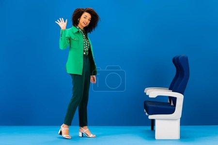 Photo pour Femme afro-américaine souriante agitant et debout près des sièges sur fond bleu - image libre de droit
