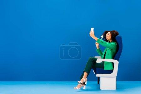 Photo pour Femme afro-américaine souriante prenant selfie avec passeport et billet d'avion sur fond bleu - image libre de droit