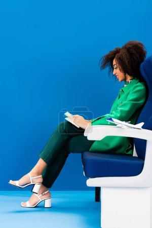 Photo pour Vue latérale de la femme afro-américaine souriante et modèle d'avion sur siège sur fond bleu - image libre de droit