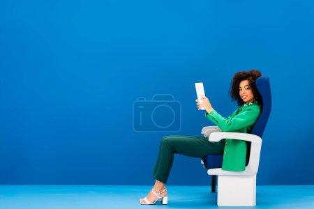 Photo pour Une Américaine africaine souriante assise sur son siège et tenant une tablette numérique sur fond bleu - image libre de droit