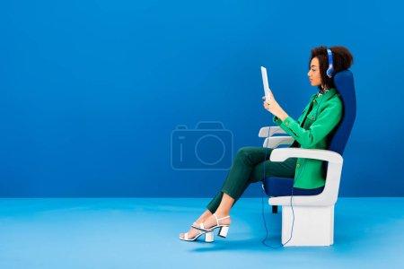 Photo pour Vue latérale d'un Africain américain utilisant une tablette numérique et écoutant de la musique sur fond bleu - image libre de droit