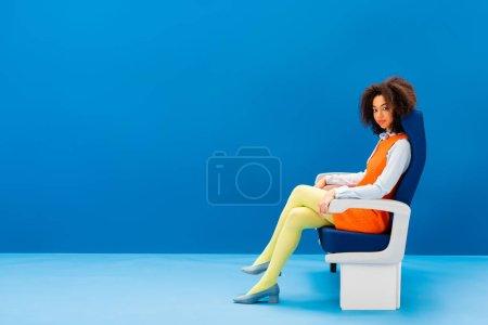 Foto de Africano americano vestido de retro sentado en el asiento sobre fondo azul - Imagen libre de derechos