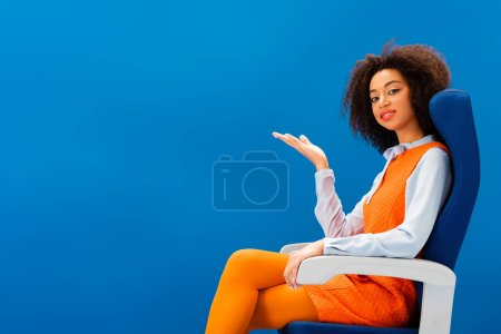 Photo pour Smiling african american in retro dress pointing with hand isolated on blue - image libre de droit
