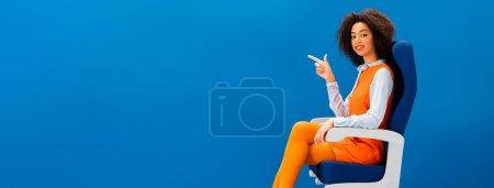 Photo pour Plan panoramique de souriant afro-américain en robe rétro assis sur le siège et pointant du doigt isolé sur bleu - image libre de droit