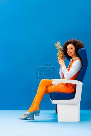 Photo pour Un américain africain souriant en robe rétro assis sur son siège et tenant l'ananas sur fond bleu - image libre de droit