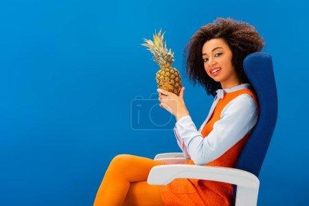 Photo pour Un américain africain souriant en robe rétro assis sur son siège et tenant l'ananas isolé en bleu - image libre de droit