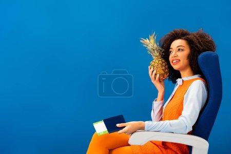 Photo pour Un Américain d'origine africaine souriant en robe rétro tenant ananas et passeport avec billet d'avion isolé sur bleu - image libre de droit
