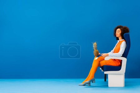 Photo pour Africain américain en robe rétro dormant et tenant un ananas sur fond bleu - image libre de droit