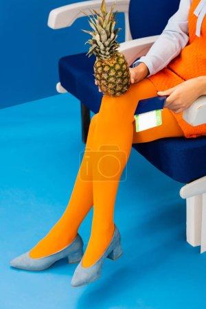 Photo pour Crochet vue d'un Africain américain en robe rétro tenant ananas et passeport avec billet d'avion sur fond bleu - image libre de droit