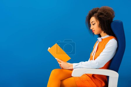 Photo pour Side view of african american in retro dress sitting on seat and reading book isolated on blue - image libre de droit