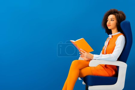 Photo for Smiling african american in retro dress sitting on seat and holding book isolated on blue - Royalty Free Image