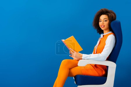 Photo for Smiling african american in retro dress holding book and sitting on seat isolated on blue - Royalty Free Image