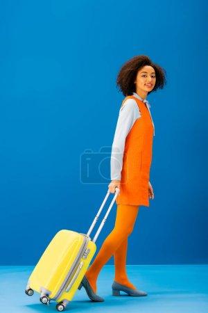 Photo pour Souriant afro-américain en robe rétro marche avec sac de voyage sur fond bleu - image libre de droit