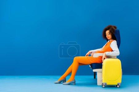 Photo pour Africain américain en robe rétro assis sur son siège près d'un sac de voyage sur fond bleu - image libre de droit
