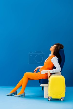 Photo pour Side view of african american in retro dress sleeping in seat on blue background - image libre de droit