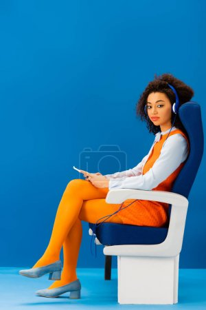 Photo for African american in retro dress sitting on seat and listening to music on blue background - Royalty Free Image