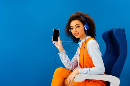 african american in retro dress listening to music and holding smartphone isolated on blue