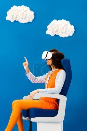 Photo pour Vue latérale de l'afro-américain avec casque vr pointant du doigt sur fond bleu avec nuages - image libre de droit
