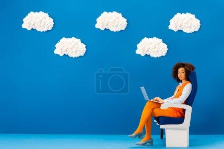 Photo pour Afro-américaine en robe rétro assise sur un siège et tenant un ordinateur portable sur fond bleu avec des nuages - image libre de droit