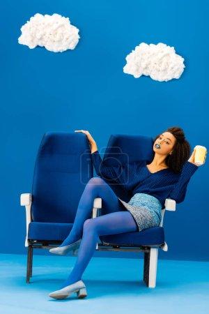 Photo pour Afro-américain assis sur un siège et tenant une tasse en papier sur fond bleu avec des nuages - image libre de droit