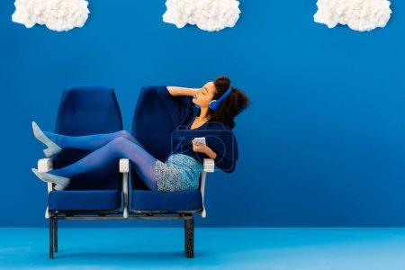 Photo pour Vue latérale d'afro-américain assis sur des sièges, écoutant de la musique sur fond bleu avec des nuages - image libre de droit