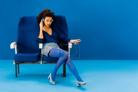 Photo for African american sitting on seat, listening to music and holding smartphone on blue background - Royalty Free Image