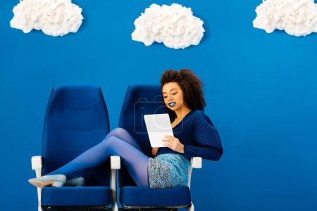 smiling african american sitting on seats and using digital tablet on blue background with clouds