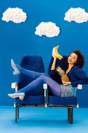 smiling african american sitting on seats and holding bananas and pineapple on blue background with clouds