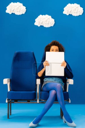 Photo for African american obscuring face with laptop and sitting on seat on blue background with clouds - Royalty Free Image