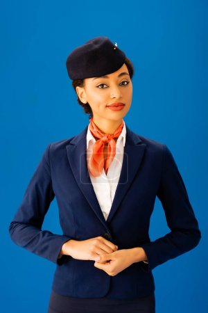 Photo for Smiling african american flight attendant  looking at camera isolated on blue - Royalty Free Image