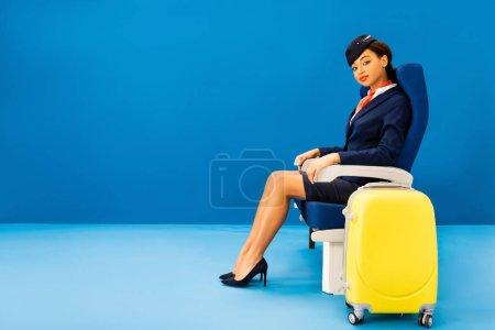 Photo pour Agent de bord afro-américain assis sur un siège près d'un sac de voyage sur fond bleu - image libre de droit