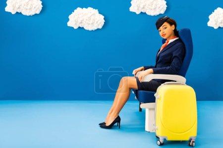 Photo pour Agent de bord afro-américain assis sur un siège près du sac de voyage sur fond bleu avec des nuages - image libre de droit