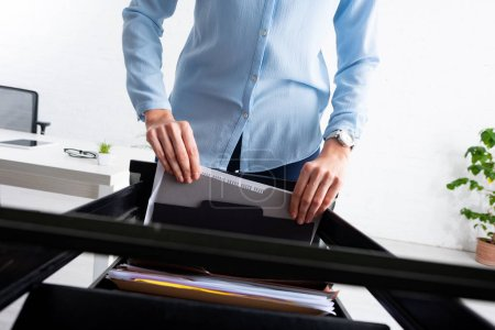 Ausgeschnittene Ansicht einer Geschäftsfrau, die Ordner mit Dossier von einem offenen Kabinettsfahrer im Büro mitnimmt