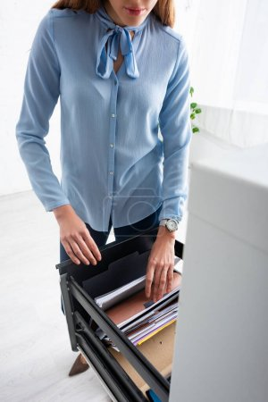 Foto de Enfoque selectivo de la mujer de negocios que busca dossier en el controlador del gabinete - Imagen libre de derechos