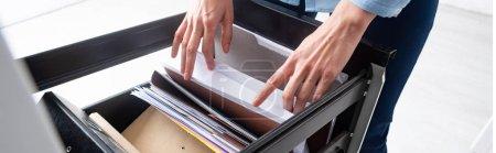 Photo pour Vue recadrée d'une femme d'affaires cherchant un dossier dans des dossiers papier dans un pilote d'armoire, panoramique - image libre de droit