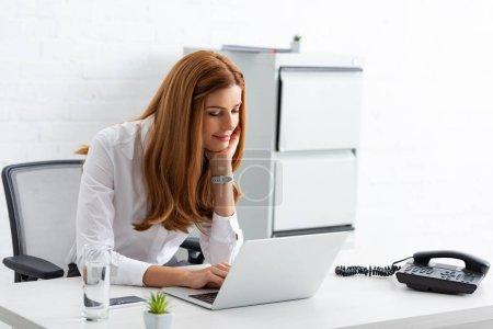 Photo pour Femme d'affaires souriante utilisant un ordinateur portable près du téléphone sur la table - image libre de droit