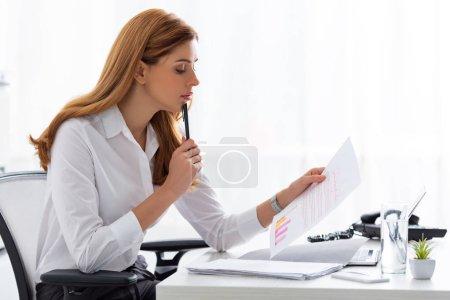 Photo pour Vue latérale de la femme d'affaires tenant du papier avec des graphiques près des documents et ordinateur portable sur la table - image libre de droit