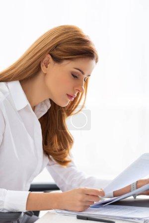 Photo pour Vue latérale d'une femme d'affaires séduisante tenant un dossier près de documents sur table - image libre de droit