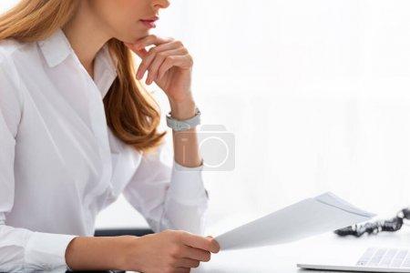 Photo pour Vue recadrée d'une femme d'affaires avec la main près du menton tenant un dossier à table - image libre de droit