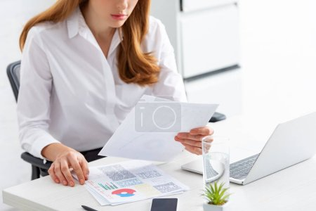Photo for Cropped view of businesswoman holding paper with graphs near smartphone and laptop on table - Royalty Free Image