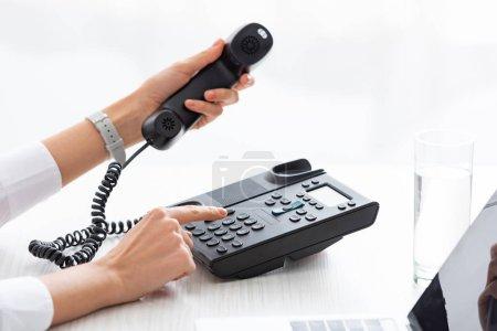 Photo pour Vue recadrée de femme d'affaires en utilisant le téléphone près du verre d'eau et ordinateur portable sur la table - image libre de droit