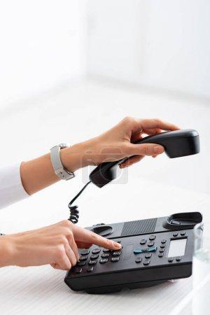 Photo pour Vue recadrée de femme d'affaires en utilisant le téléphone près du verre d'eau sur la table - image libre de droit