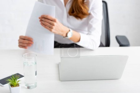 Photo for Selective focus of laptop and glass of water and businesswoman holding documents at table - Royalty Free Image