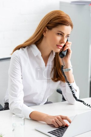 Photo for Successful businesswoman using laptop and talking on phone at office table - Royalty Free Image