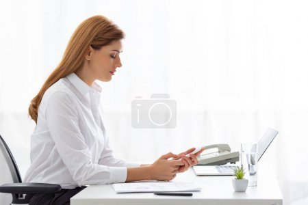 Photo for Side view of businesswoman using smartphone near documents and laptop on table - Royalty Free Image