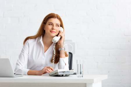 Foto de Smiling business woman looking away while speaking on phone at table in office - Imagen libre de derechos