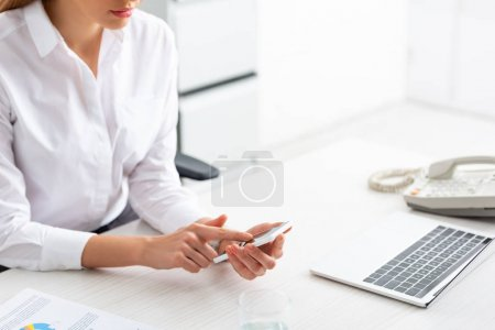 Photo for Cropped view of businesswoman using smartphone near document with chart and laptop on table - Royalty Free Image